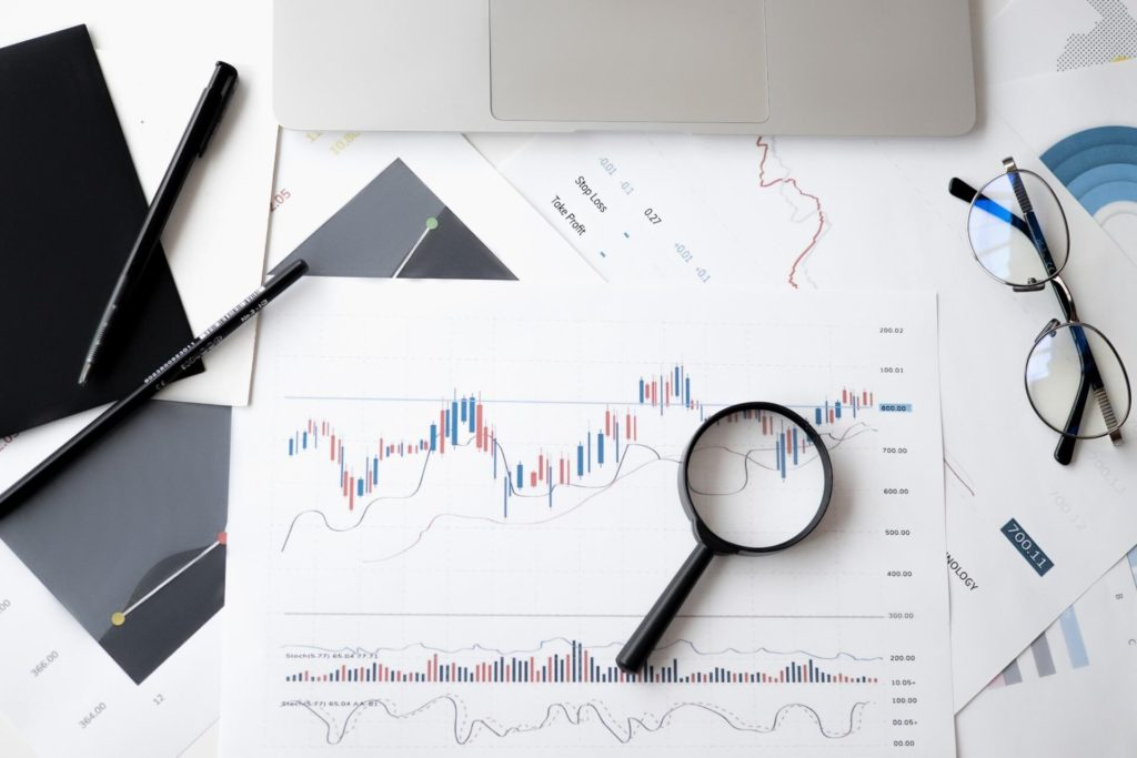 Charts of profit growths and falls next to glasses and magnifying glass